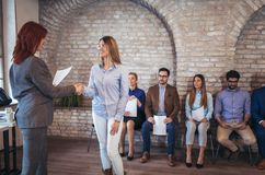Businesswoman shaking hands with woman besides people waiting for job interview. Businesswoman shaking hands with women besides people waiting for job interview Royalty Free Stock Image