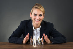 Businesswoman Sheltering Paper Team On Desk. Smiling young businesswoman sheltering paper team on desk over gray background Stock Photography