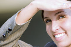 Businesswoman shielding eyes with hand, smiling, close-up, portrait Royalty Free Stock Photos