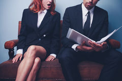 Businesswoman is shocked after reading document. Businesswoman is shocked after reading a document her male coworker is holding Stock Photos