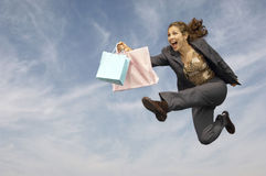 Businesswoman With Shopping Bags Running Against Cloudy Sky Stock Images
