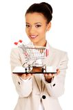Businesswoman with shopping cart and tablet. Stock Images