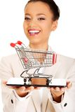 Businesswoman with shopping cart and tablet. Stock Photos