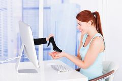 Businesswoman shopping shoes online at computer desk Royalty Free Stock Images