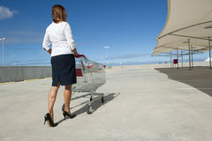 Businesswoman and shopping trolley Royalty Free Stock Photography