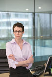Businesswoman, with short hair and spectacles, leaning against desk in office, arms folded, portrait Royalty Free Stock Image