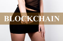 Businesswoman in short skirt pressing blockchain button of a virtual screen. exchange and production of crypto currency Royalty Free Stock Photos