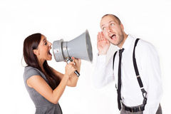 Businesswoman shouting at a businessman with megaphone Royalty Free Stock Images