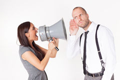 Businesswoman shouting at a businessman with megaphone Royalty Free Stock Photography
