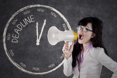 Businesswoman is shouting deadline with megaphone. Image of a businesswoman shouting with megaphone and big clock with deadline text on the blackboard Royalty Free Stock Photo