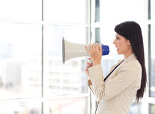 Businesswoman shouting in a megaphone Royalty Free Stock Photography