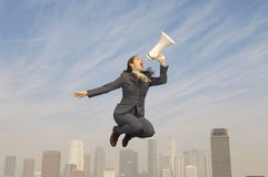 Businesswoman Shouting Into Megaphone Above City Stock Photography