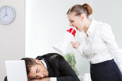 Businesswoman shouting in megaphone. Against a colleague Royalty Free Stock Photos