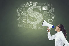 Businesswoman shouting on megaphone. With business and finance icons on chalkboard Stock Photo