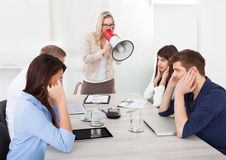 Businesswoman shouting through megaphone on colleagues Royalty Free Stock Photo