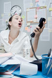 Businesswoman shouting at phone. Angry stressed businesswoman in office shouting at phone Royalty Free Stock Photos