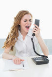 Businesswoman shouting into the phone at office Royalty Free Stock Images