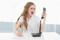 Businesswoman shouting into the phone at office Royalty Free Stock Image