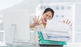 Businesswoman shouting with stack of folders at desk Royalty Free Stock Image