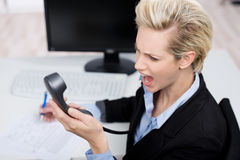 Businesswoman Shouting On Telephone Receiver At Desk Royalty Free Stock Photos