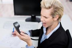 Businesswoman Shouting On Telephone Receiver At Desk. Frustrated young businesswoman shouting on telephone receiver at office desk Royalty Free Stock Photos