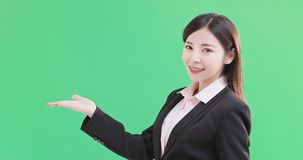 Businesswoman show something. To you on the green background stock photography