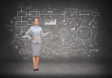 Businesswoman showing big plan on concrete wall Stock Photo