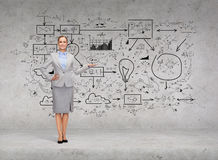 Businesswoman showing big plan on concrete wall Royalty Free Stock Photo
