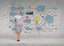 Businesswoman showing big plan on concrete wall Royalty Free Stock Photos