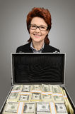 Businesswoman showing a briefcase full of money - isolated Royalty Free Stock Photos