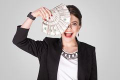 Businesswoman showing at cash, dollar and toothy smile. Studio shot, indoor. Isolated on grey background Stock Photos
