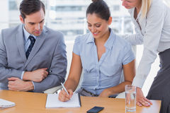 Businesswoman showing colleagues something on notepad Stock Image