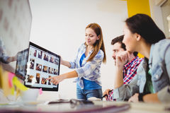 Businesswoman showing computer screen to coworkers Stock Images