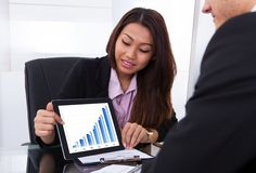 Businesswoman showing digital tablet to colleague Stock Images