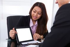 Businesswoman showing digital tablet to colleague Royalty Free Stock Photography