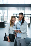 Businesswoman showing digital tablet to colleague Royalty Free Stock Photos