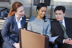 Businesswoman showing document from briefcase to two colleagues on train station platform, smiling Royalty Free Stock Photography
