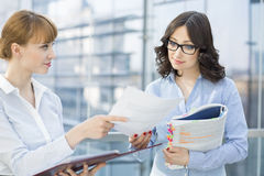 Businesswoman showing document to female colleague in office stock photo