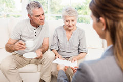 Businesswoman showing documents to senior couple Royalty Free Stock Photos