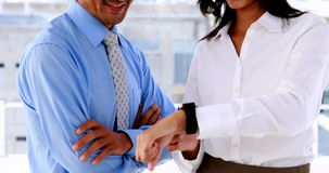 Businesswoman showing her smart watch to colleague stock video