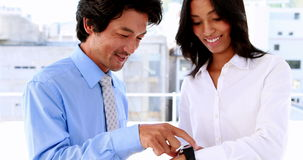 Businesswoman showing her smart watch to colleague stock footage