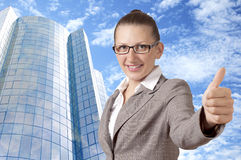 Businesswoman showing his thumb up with smile. Happy businesswoman showing his thumb up with smile, office building background Stock Images