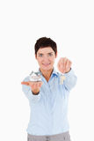 Businesswoman showing keys and a miniature house Royalty Free Stock Photos