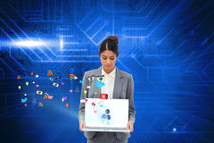 Businesswoman showing laptop with app icons Stock Photo