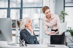 Businesswoman showing laptop to senior colleague sitting at workplace. Young businesswoman showing laptop to senior colleague sitting at workplace stock photography