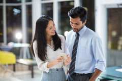 Businesswoman showing mobile phone to colleague Stock Photography