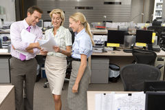 Businesswoman showing paperwork to colleagues in office, smiling, elevated view Stock Photography