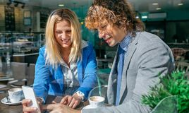 Businesswoman showing phone to coworker. Businesswoman showing something on the phone to coworker in a coffee shop Royalty Free Stock Image