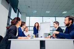 Business woman giving presentation to colleagues in office. Businesswoman showing project on flipchart while giving presentation to colleagues in office Royalty Free Stock Images