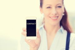 Businesswoman showing smart phone, contract sign on screen. Smiling businesswoman showing smart phone, contract sign on screen isolated outside city background Stock Photography